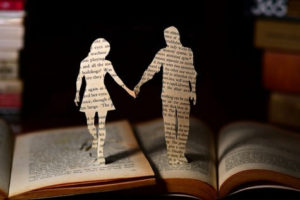A paper cut out of man and woman holding hands in a book - 7 Unromantic ways to keep marriage strong and healthy